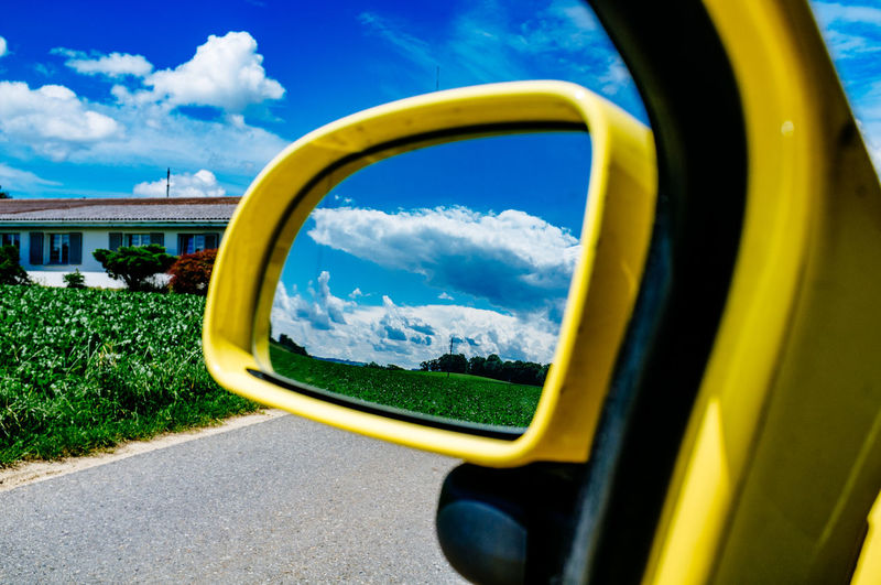 Reflection Of Cloudy Sky In Side Mirror
