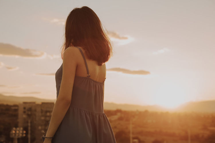 Adult Brown Hair Cloud - Sky Hairstyle Land Leisure Activity Lens Flare Lifestyles Long Hair Looking At View Nature One Person Outdoors Real People Rear View Sky Standing Sunlight Sunset Three Quarter Length Women Young Adult The Traveler - 2018 EyeEm Awards