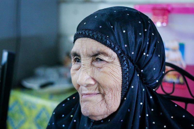 Close-up of senior woman wearing hijab at home