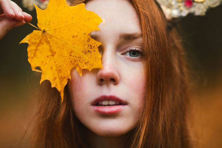Close-up portrait of young woman holding maple leaf