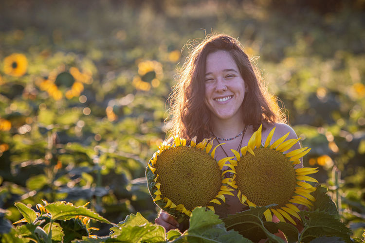 Portrait of smiling woman in sunflower farm