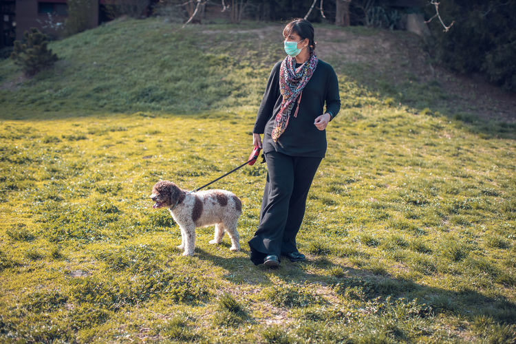 Full length of woman with dog standing on field
