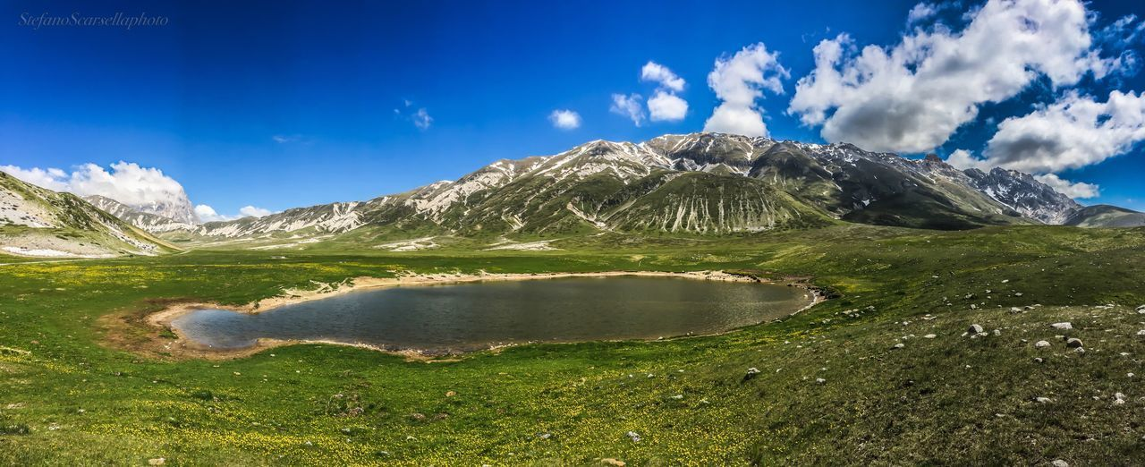 mountain, nature, tranquil scene, scenics, beauty in nature, sky, tranquility, cloud - sky, mountain range, landscape, outdoors, day, blue, lake, grass, green color, physical geography, water, no people