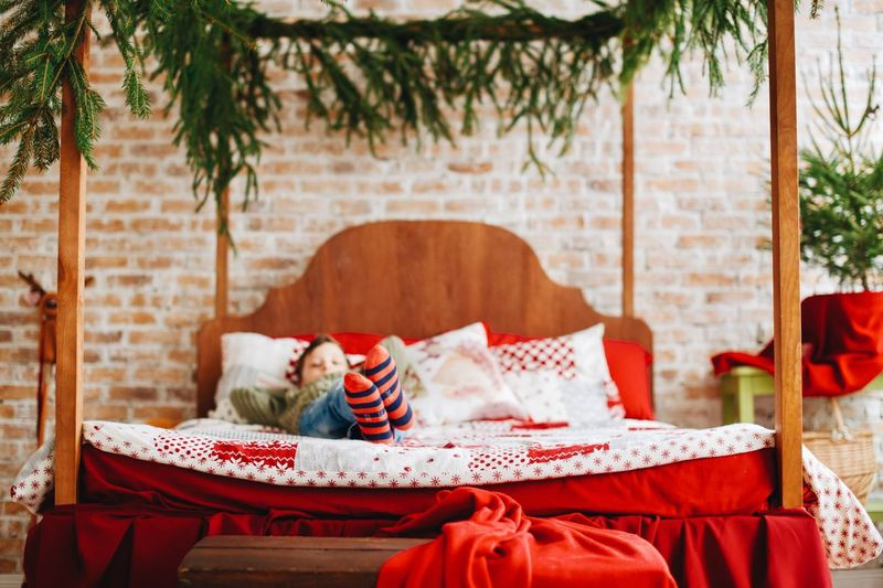 Boy Lying In Bed During Christmas At Home