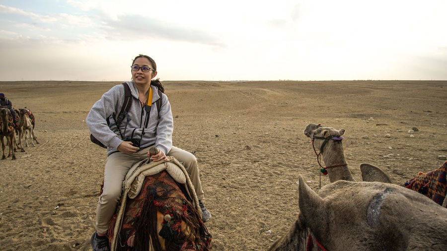 Asian woman tourist riding on camel for pyramid attraction view in egypt