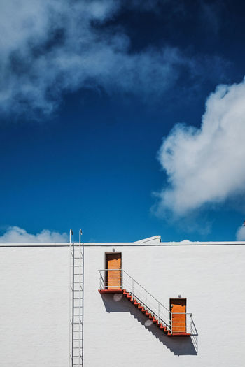 Low angle view of steps on wall against sky