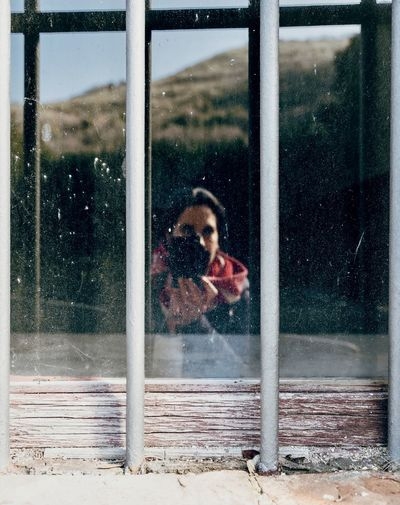 Woman with dog seen through glass window