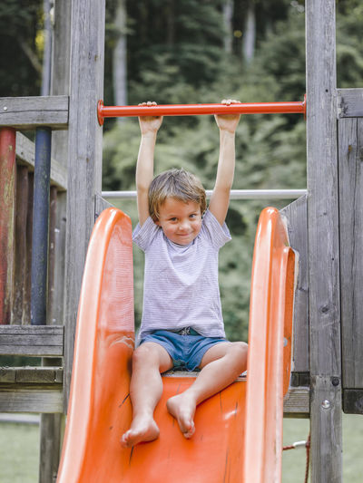 Portrait of smiling boy sliding at playground