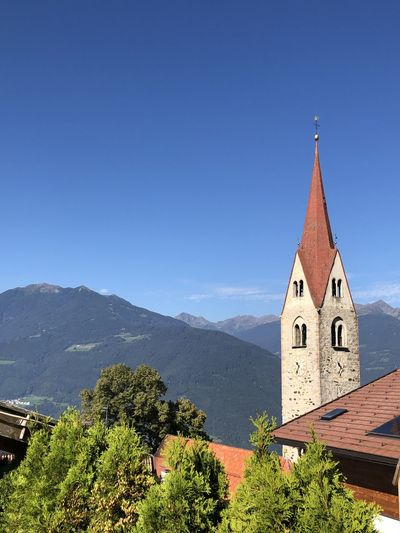 Panoramic view of building and mountains against clear blue sky