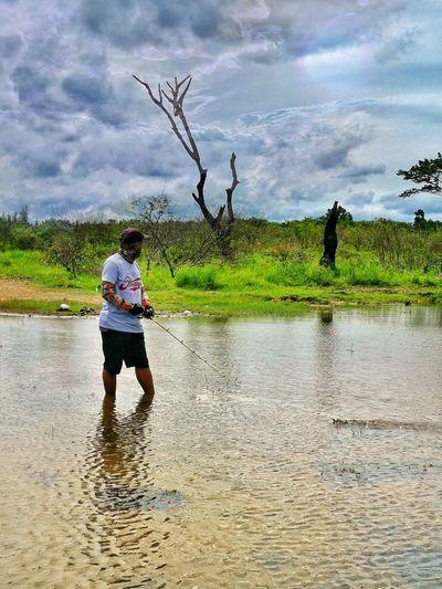 Full length of boy standing by lake against sky