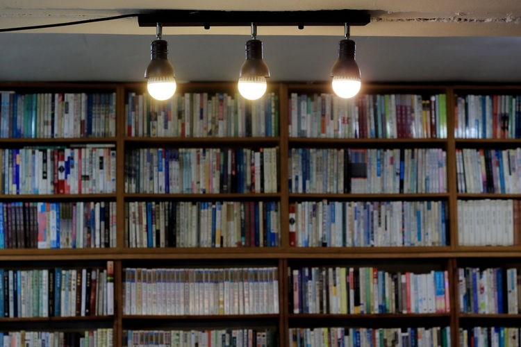 Illuminated lights with books in shelves in background