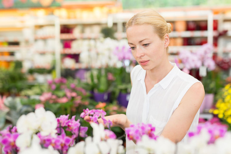 Beautiful woman standing at flower shop