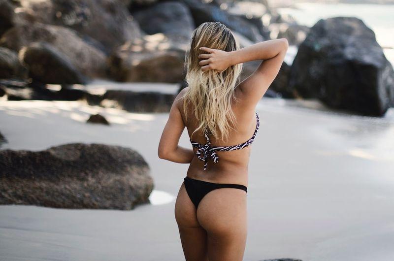 Rear view of woman in bikini standing at beach
