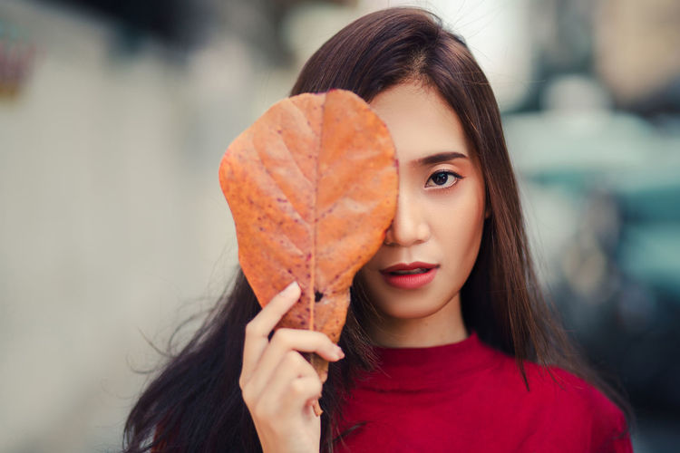 Portrait of young woman holding leaf outdoors