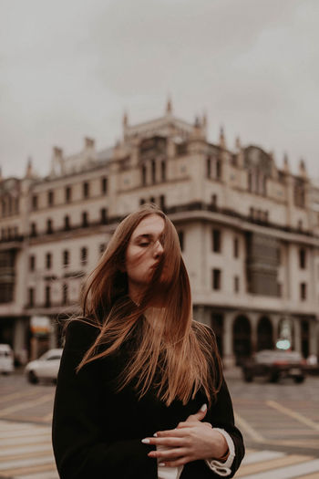 Beautiful woman standing in city against sky