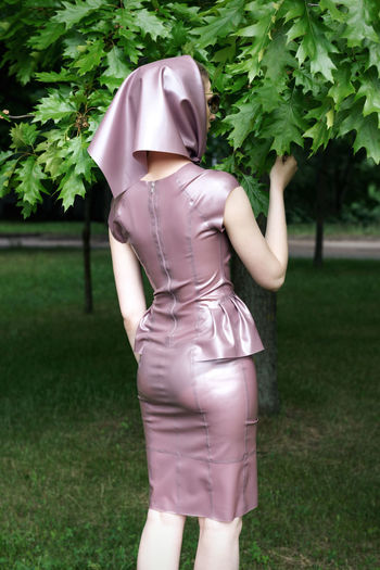 Rear view of woman wearing dress standing by plants in park
