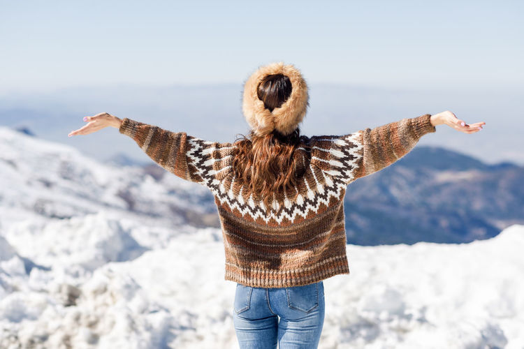 Rear view of woman standing with arms outstretched on snow against sky
