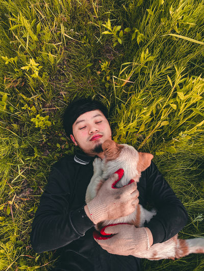 Young man with dog against plants