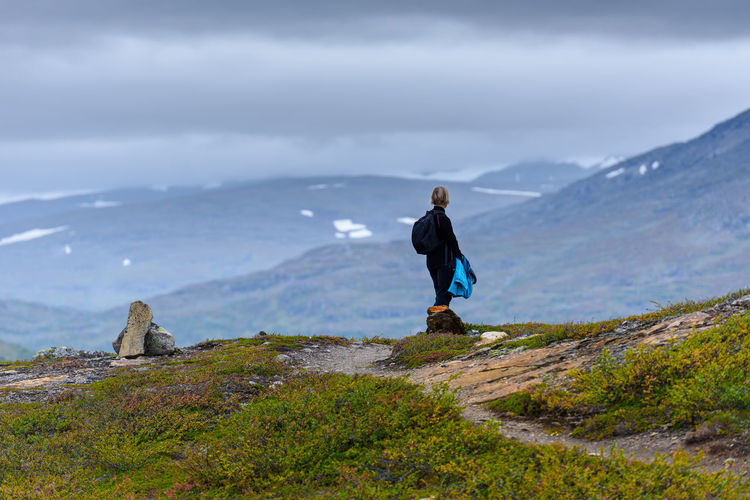 Side View Of Senior Woman Standing On Mountain Against Cloudy Sky