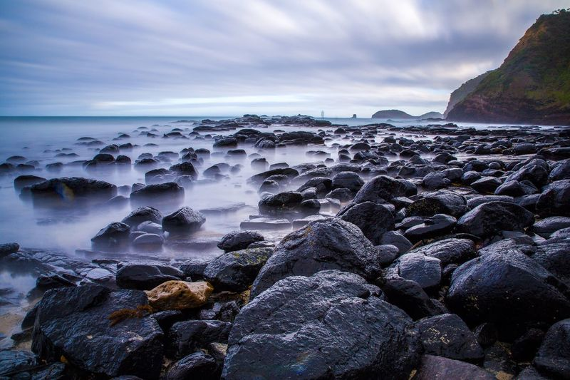 Rocky Coastline Against Cloudy Sky