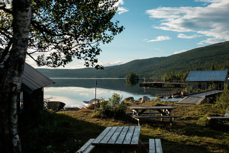 Picnic tables and boats at a lake in sweden. No people Arrival Beach Beauty In Nature Camping Coastline Day Idyllic Landscape Mountain Mountain Range Nature Nautical Vessel No People Outdoors Scenics Sea Sky Summer Tourism Travel Travel Destinations Tree Vacations Village Water
