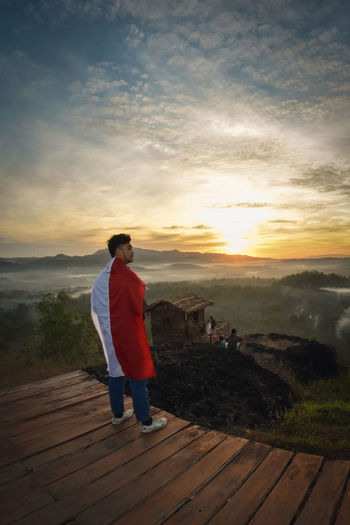 Rear view of man with indonesian flag standing on wood during sunset