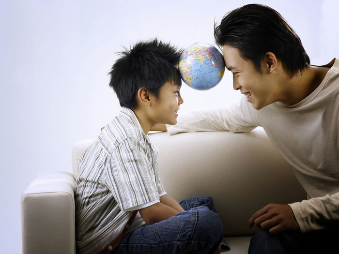 Father and son with globe sitting against wall on sofa