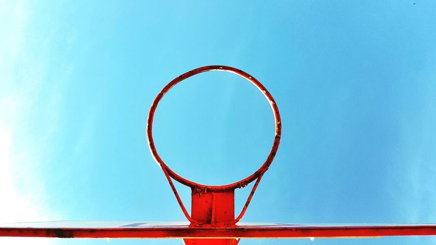 Close-up of basketball hoop against blue sky