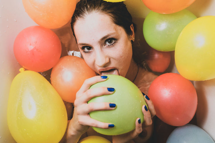 Portrait Of Woman Licking Colorful Balloons At Home