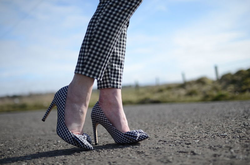 Low section of woman in checked pattern high heels and cloth on road