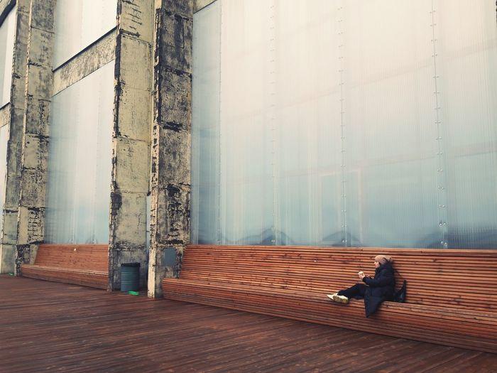 Man sitting on hardwood floor against wall