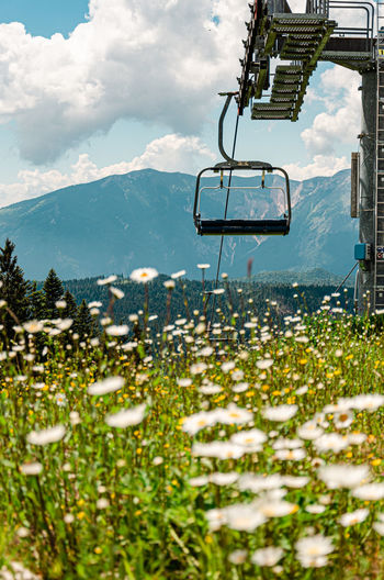 Ski lift over mountains against sky