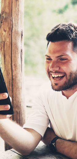 Happy young man looking at mobile phone