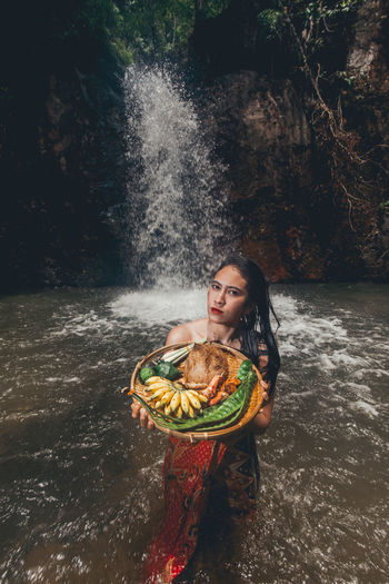 Portrait of young woman holding plate while standing in river against waterfall