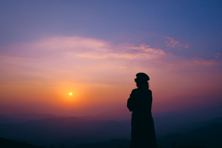 Silhouette women standing against orange sky on mountain.
