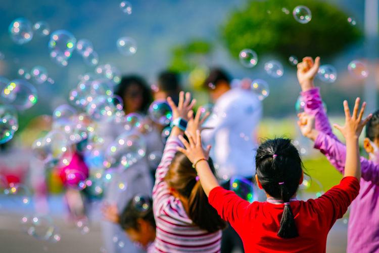 Rear view of girl enjoying bubbles outdoors