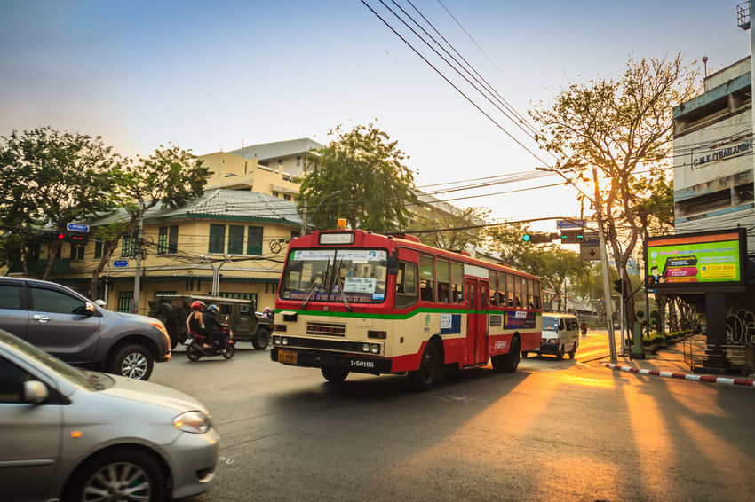 Bangkok, Thailand - March 2, 2017: Local bus and cars in traffic passes through a busy junction during sunset in Bangkok, Thailand. Sunlight Traffic Traffic Jam Traffic Signs Trafficlight Architecture Building Exterior Built Structure Cable Car City City Life Day Electricity  Incidental People Junctionsquare Land Vehicle Mode Of Transportation Motion Motor Vehicle Nature on the move Public Transportation Road Sky Street Sunbeam Sunrise Sunset Sunshine Traffic Arrow Sign Traffic Control Traffic Flow Traffic Light  Traffic Lights Traffic Sign Traffic Signal Trafficjam Trafficlights Transportation