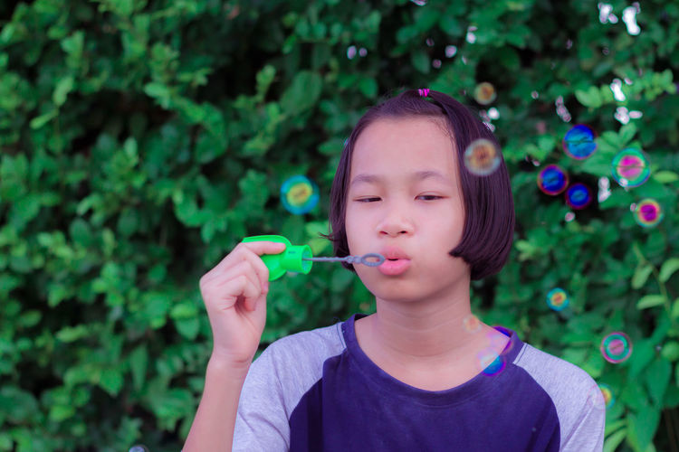 Girl blowing bubbles against plants