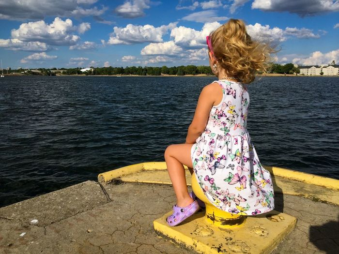 Girl sitting on cleat at river against sky