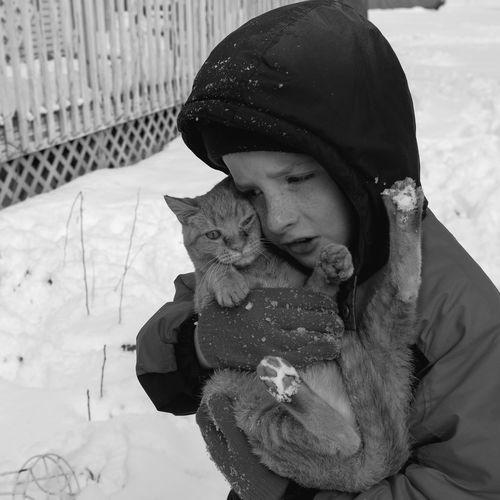 Boy hugging cat during winter