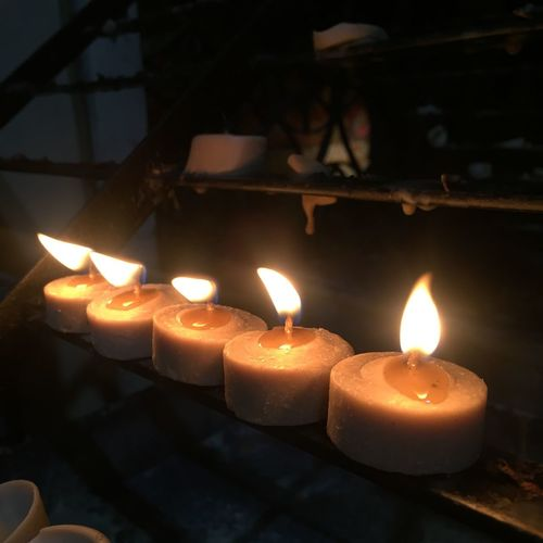 Close-up of lit tea light candles in temple