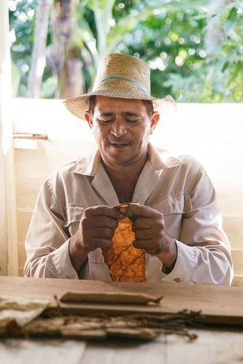 Man wearing hat holding leaf