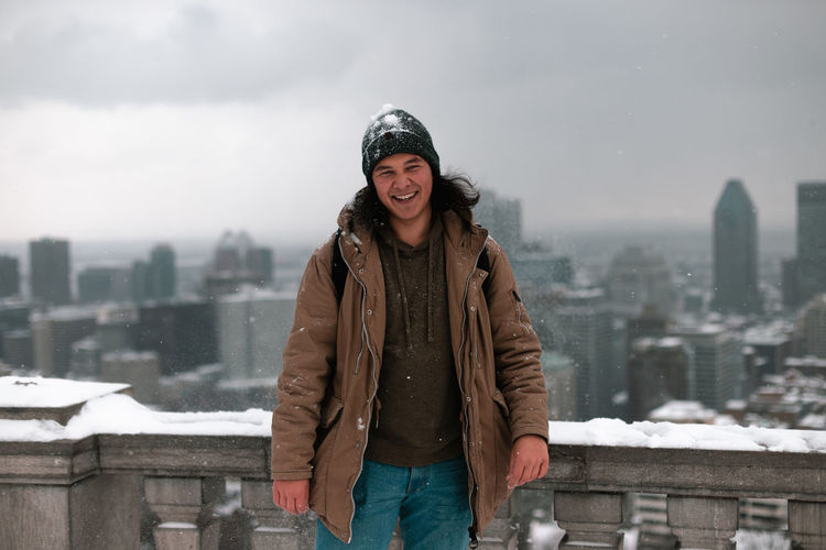 Portrait of smiling man standing against cityscape during winter