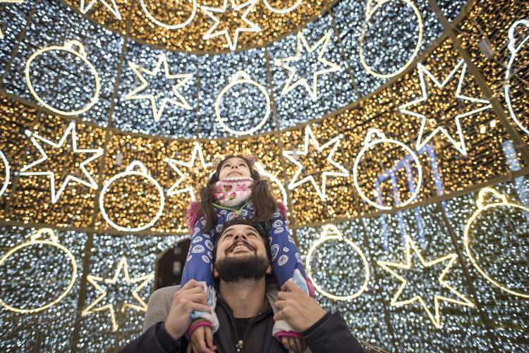 Father piggybacking daughter by illuminated lights