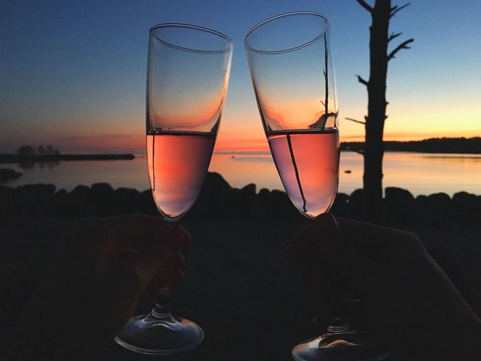 Cropped Image Of Silhouette People Tossing Champagne Flute During Sunset