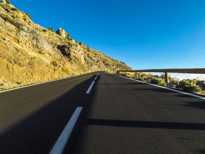 Long way road at the mountain with vulcan mount in front and blue clear sky - ground point of view with black asphalt and white lines - driving and travel concept Road Transportation Sky The Way Forward Clear Sky Direction Nature Symbol No People Road Marking Marking Sign Mountain Diminishing Perspective Day Sunlight Empty Road Blue Country Road Country Outdoors Dividing Line Asphalt Road Blue Sky El Teide National Parc Solitude Silence Sunny Freedom Adventure Dscovering Travel Destinations Vacations Backgrounds