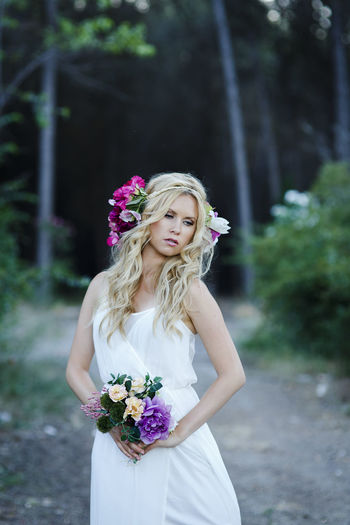 Young blond woman with blue eyes and long wavy hair in countryside. Attractive bride wearing white dress, flower hairband and holding flower bouquet Adult Beautiful Woman Bouquet Bride Celebration Flower Flower Arrangement Flowering Plant Focus On Foreground Front View Hair Hairstyle Leisure Activity Lifestyles One Person Outdoors Plant Real People Standing Wearing Flowers Wedding Women Young Adult Young Women