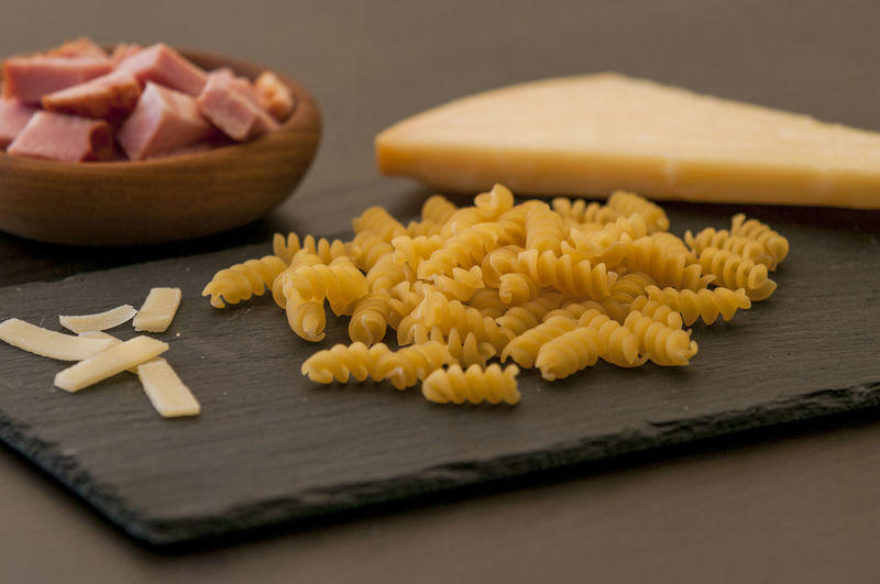 Close-up of pastas and cheese on slate