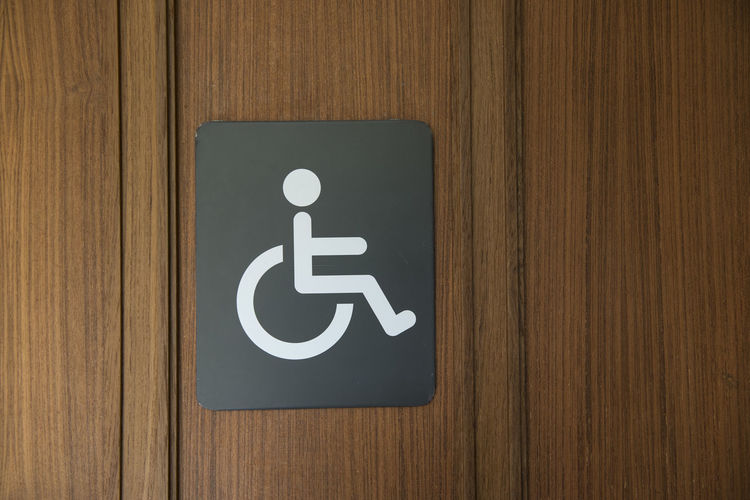 Close-up of disabled sign on wooden door