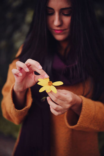 Beautiful woman holding flower standing at forest